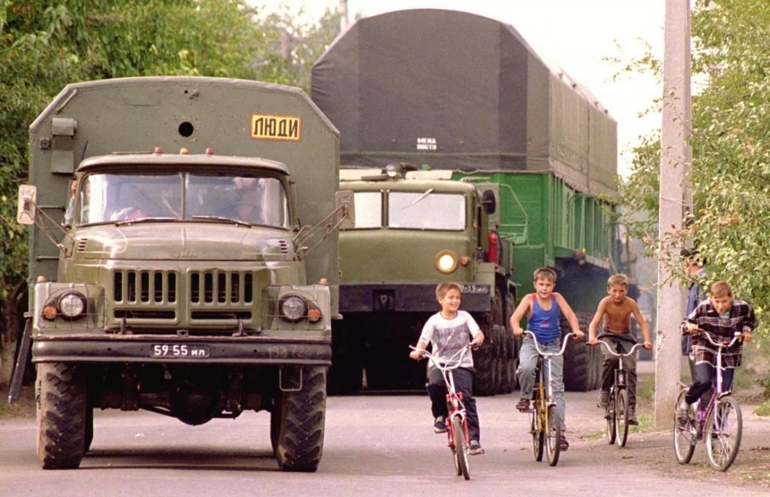 Мальчики на велосипедах едут рядом с межконтинентальной баллистической ракетой СС-24, которую перевозят к месту утилизации по улицам села Болеславчик Первомайского района Николаевской области. 31 августа 2000 года.