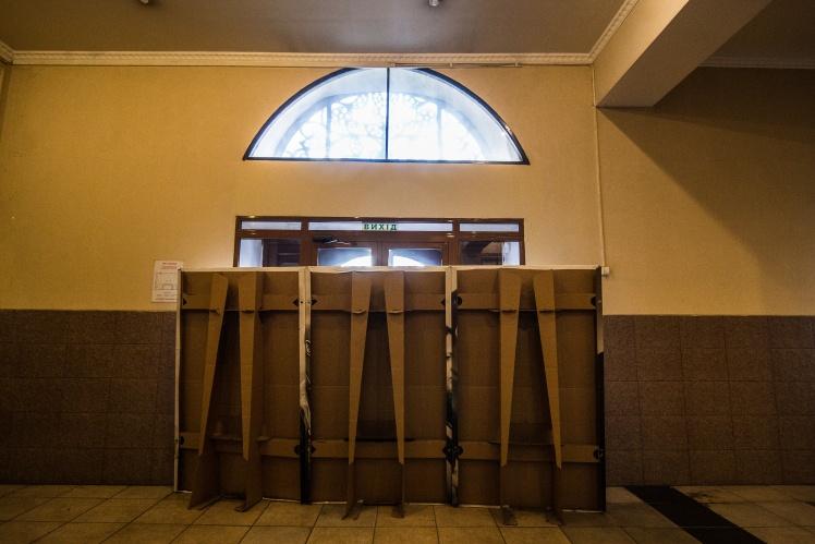 Холл кинотеатра. Входные двери закрыты и перегорожены рекламными щитами. Здесь дежурит «Мунициальная охрана».