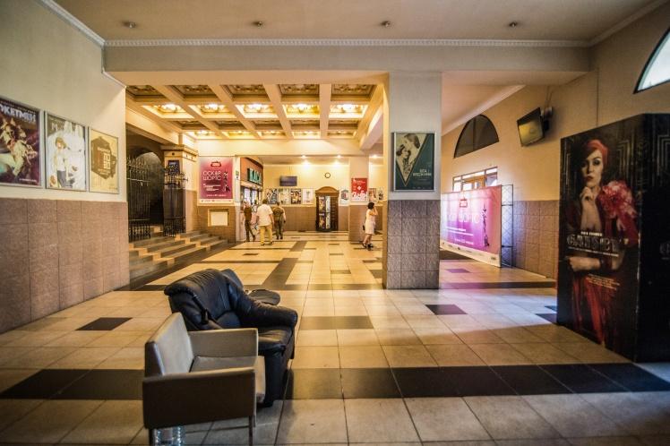 Хол кінотеатру. Вхідні двері зачинені та перегороджені рекламними щитами. Тут чергує «Муніципальна охорона».