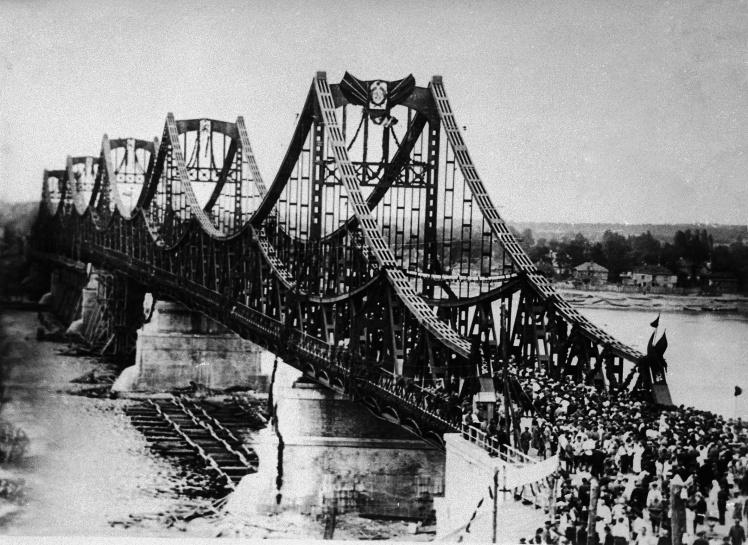 Відкриття моста імені Євгенії Бош у Києві в 1925 році. У 1941 році його підірвали радянські війська, які відступали. У 1965 році поряд з його руїнами звели міст Метро.