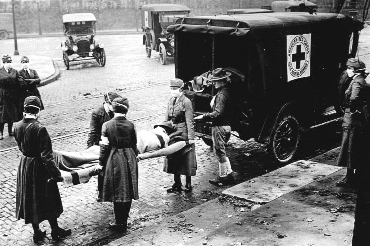 Патруль Красного Креста заносит пациента в карету скорой помощи во время эпидемии испанского гриппа в Сент-Луисе, штат Миссури, октябрь 1918 года.
