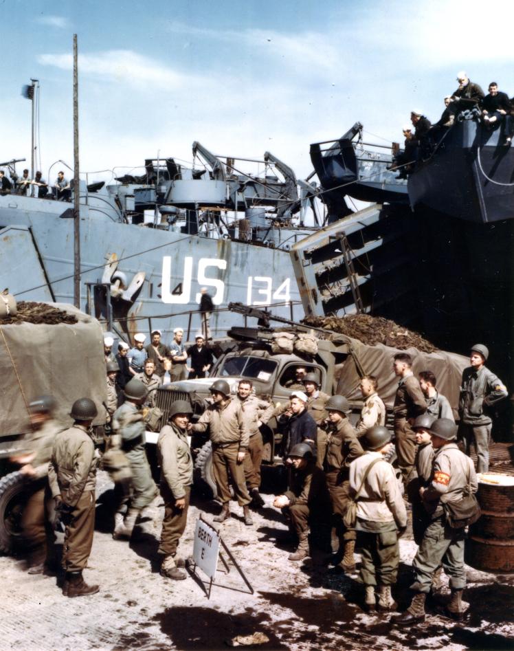 Американские военные грузовики грузят на десантный корабль во время подготовки к высадке в Нормандии, 1 июня 1944 года.