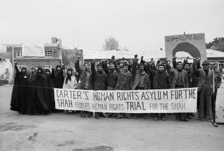 Иранские студенты, которые держат американских заложников в плену в посольстве в Тегеране, скандируют антиамериканские лозунги, 22 декабря 1979 года.