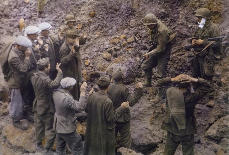 Немецкие солдаты, взятые в плен американскими войсками, недалеко от района Пуэнт-дю-Ок после высадки в Нормандии, июнь 1944 года.