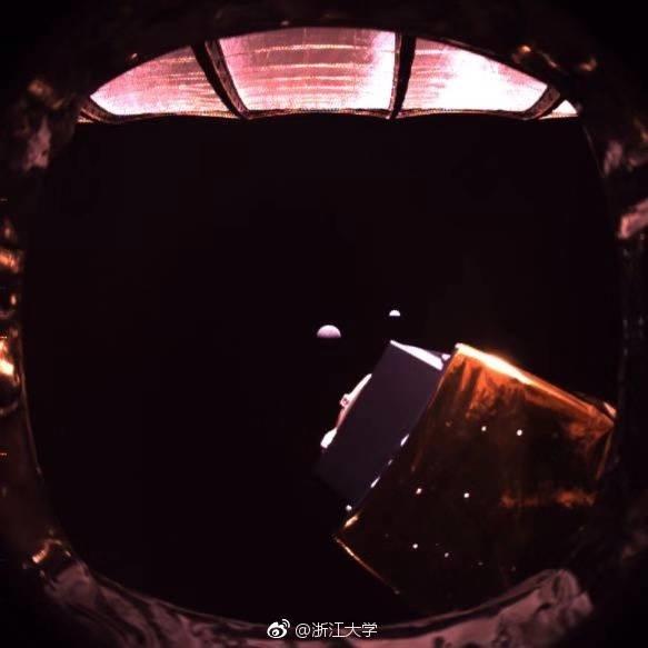 Фото зі супутника Queqiao. Більш великий коричневий об'єкт - зворотна сторона Місяця, невеликий блакитний - Земля.