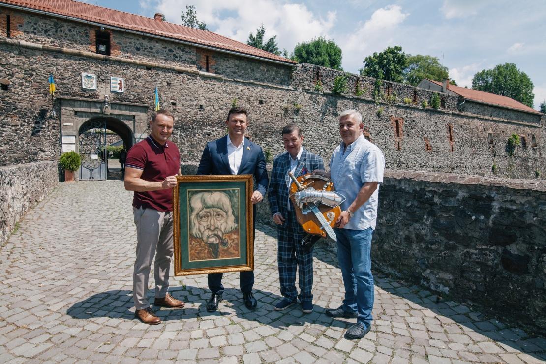 Микола Тищенко та депутат-мажоритарник від СН Михайло Лаба приймають подарунки біля входу в Ужгородський замок.