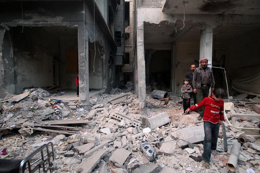 Жители Восточной Гуты среди обломков домов после авиаудара, Сирия, 18 октября 2014 года.