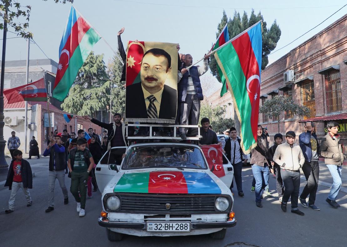 Жители азербайджанского города Гянджа с национальными флагами и портретом президента Ильхама Алиева празднуют окончание конфликта в Нагорном Карабахе, 10 ноября 2020 года.