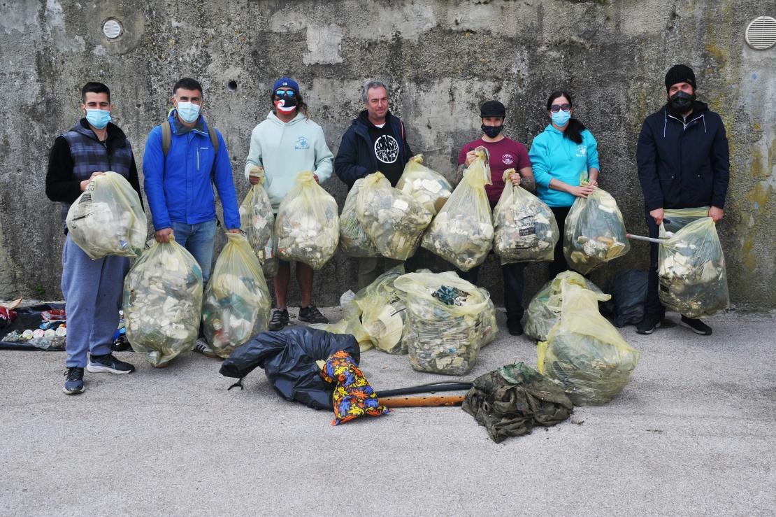 Добровольці з асоціації I pirati della Plastica і «Сини океану» позують для фото з пакетами, заповненими пластиком, знайденим у воді гавані, 18 квітня 2021 року, Ліворно, Італія.