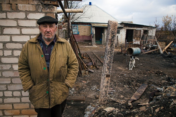 Анатолій біля флігеля, який уцілів у пожежі. Будинок праворуч згорів, жовтень 2020.
