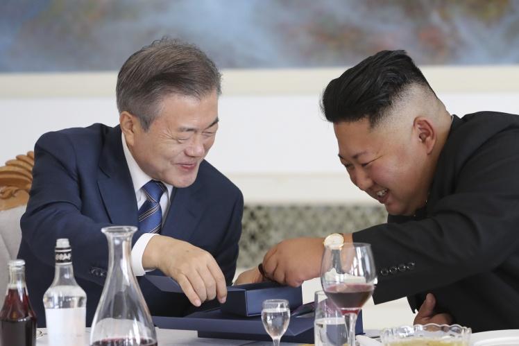 Президент Південної Кореї Мун Чже Ін (ліворуч) розмовляє з лідером Північної Кореї Кім Чен Ином (праворуч) під час обіду в ресторані 19 вересня 2018 року. Тоді відбулась зустріч на міжкорейському саміті, де вони обговорювали шляхи денуклеаризації Корейського півострова.