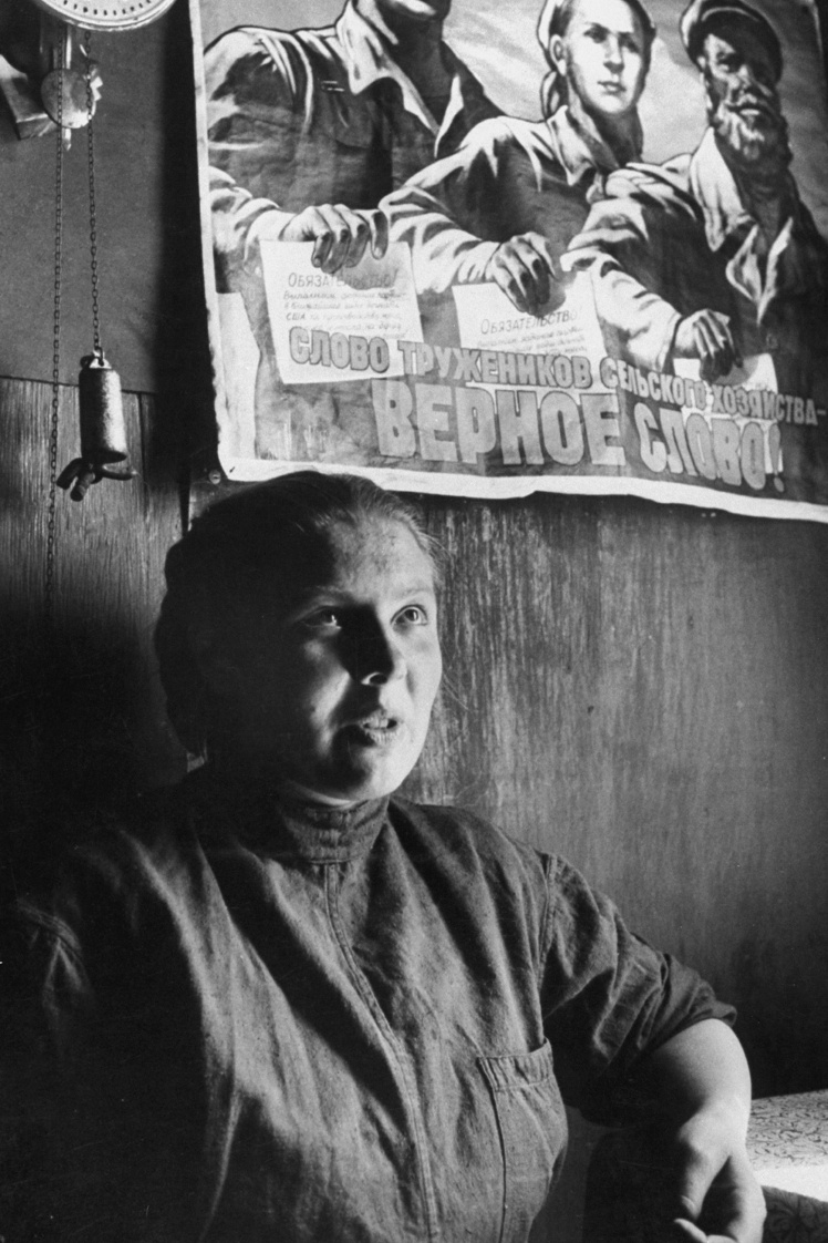 Советская колхозница сидит под агитационным плакатом, 1958 год.
