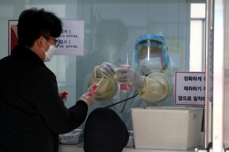 Медицинский работник берет образцы у людей в центре предварительного тестирования в Сеуле, 12 декабря 2020 года.