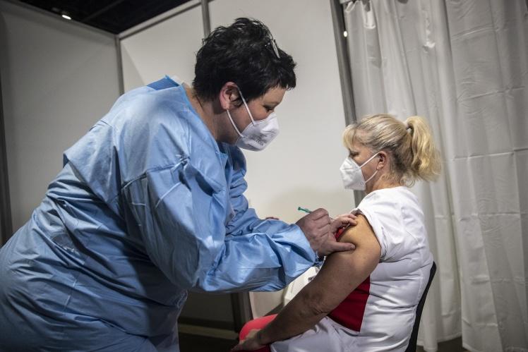 Лікар вводить вакцину Pfizer/BioNTech медичному працівнику центру вакцинації в Саксонії, Німеччина, 11 січня 2021 року.