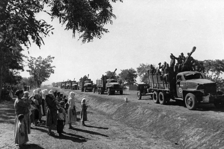 Колонна советских войск проезжает мимо группы румынских сельских жителей на американских грузовиках, присланных по ленд-лизу, сентябрь 1944 года.