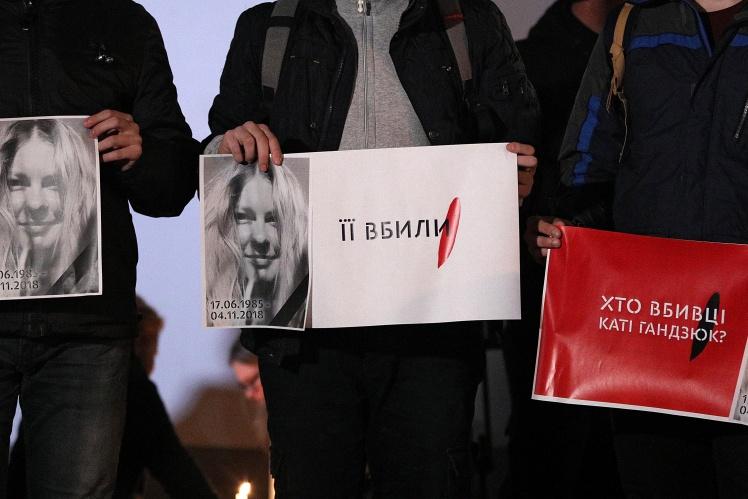 Люди тримають у руках плакати з написами «Її вбили» і «Хто вбивці Каті Гандзюк?» під час акції біля будівлі МВС, 4 листопада 2018 року.