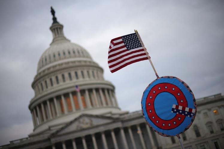 Сторонники Дональда Трампа держат флаг с символом движения QAnon на фоне Капитолия. Вашингтон, 6 января 2021 года.