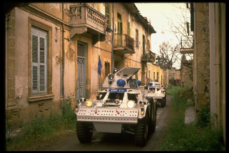 Бронемашини миротворчої місії ООН патрулюють «зелену лінію» на Кіпрі, яка проходить між покинутими будинками, березень 1989 року.