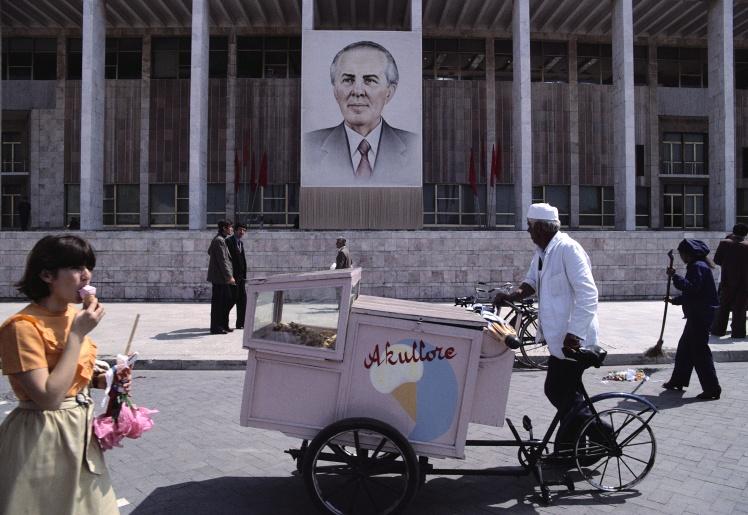 Продавець морозива і пішоходи проходять повз будівлю з портретом Енвера Ходжі, 1980 рік.