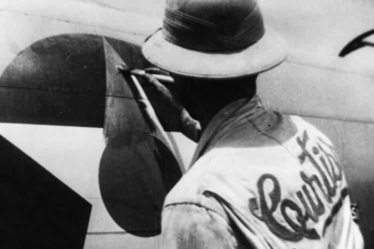 Рабочий закрашивает красной краской американский знак различия на истребителе для доставки самолета в СССР по трансиранскому коридору, 1943—1945 годы.