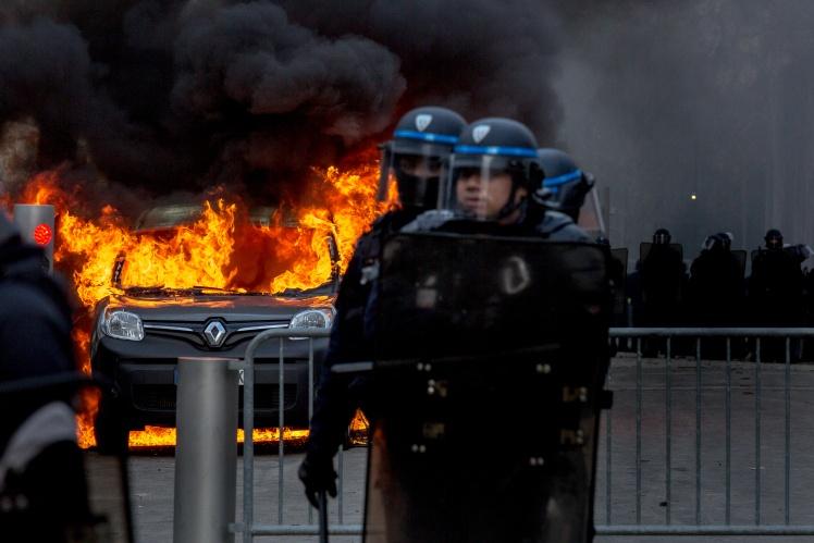 Поліцейські охороняють район перед Ейфелевою вежею в Парижі, де протестуючі «жовті жилети» підпалили автомобіль, 9 лютого 2019 року.