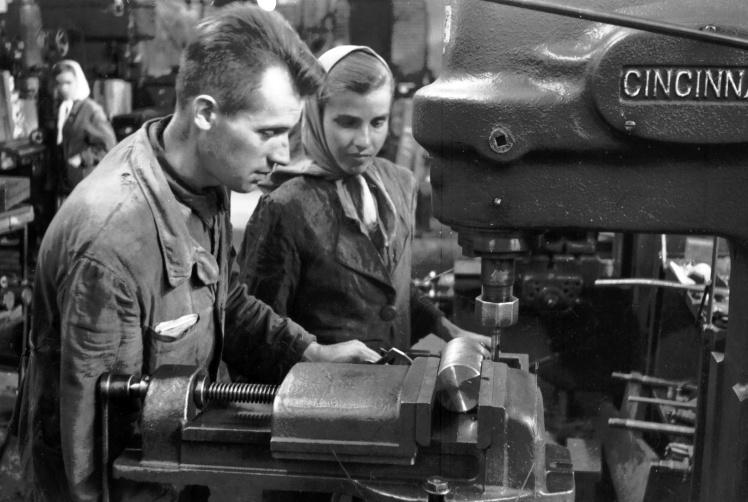 Фрезерувальник Харківського заводу транспортного машинобудування Єфімов В. С. пояснює методи роботи своїй учениці Пушкар Г. І. біля верстата американського виробництва, 1930-ті роки.