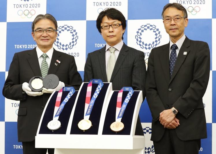 Автор дизайна медалей для Олимпийских игр в Токио 2020 года Юничи Каваниси (в центре) с комплектом олимпийских наград, 25 июля 2019 года.